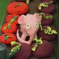 Un petit éléphant rose au milieu des rangées de légumes