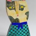 Chat tacheté à la robe à carreaux noirs et bleus. Réalisation en carton, découpage, collage, tamponnage et peinture pour les finitions.